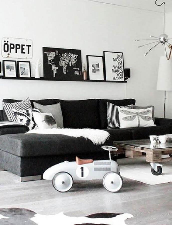 decoração de sala preto e branco com sofá sem braço e prateleira para quadros Foto Jeito de Casa