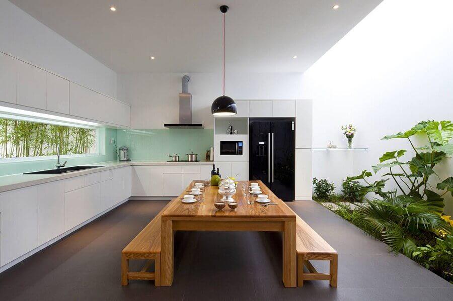 decoração moderna para cozinha externa grande planejada com armários brancos e mesa de madeira Foto ArchDaily