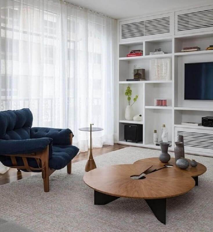 decoração moderna para sala com poltrona azul marinho de madeira e mesa de centro redonda  Foto Histórias de Casa