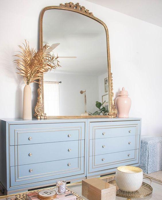 Espelho dourado na cômoda azul