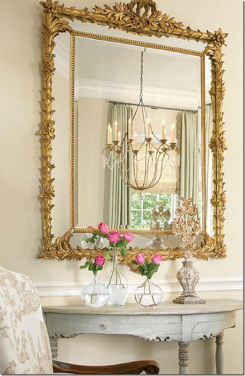 Espelho com moldura dourada na decoração da sala