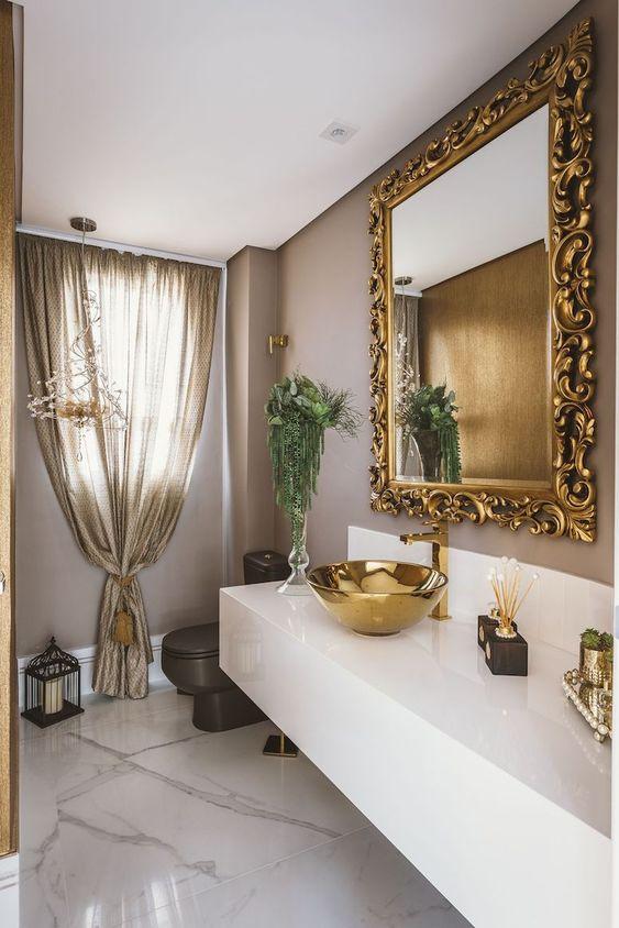 Banheiro decorado com espelho dourado
