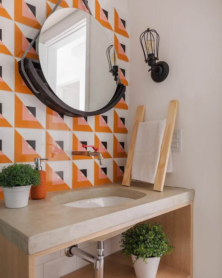 luminária de parede para banheiro decorado com espelho redondo e revestimento colorido  Foto SP Estúdio Arquitetura