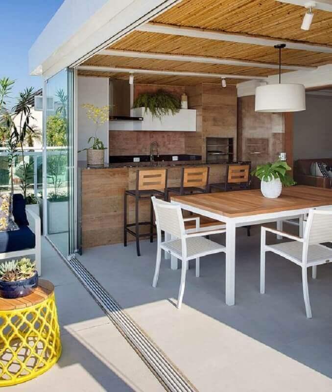 mesa branca para cozinha externa com churrasqueira e bancada de madeira Foto Arkpad