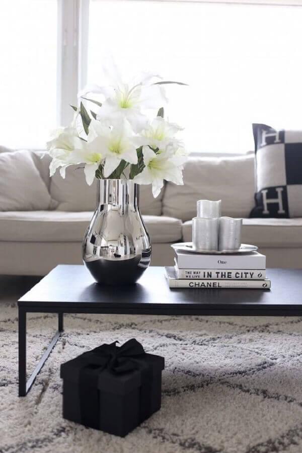 mesa de centro preta decorada com vaso de prata com flores brancas Foto Apartment Therapy