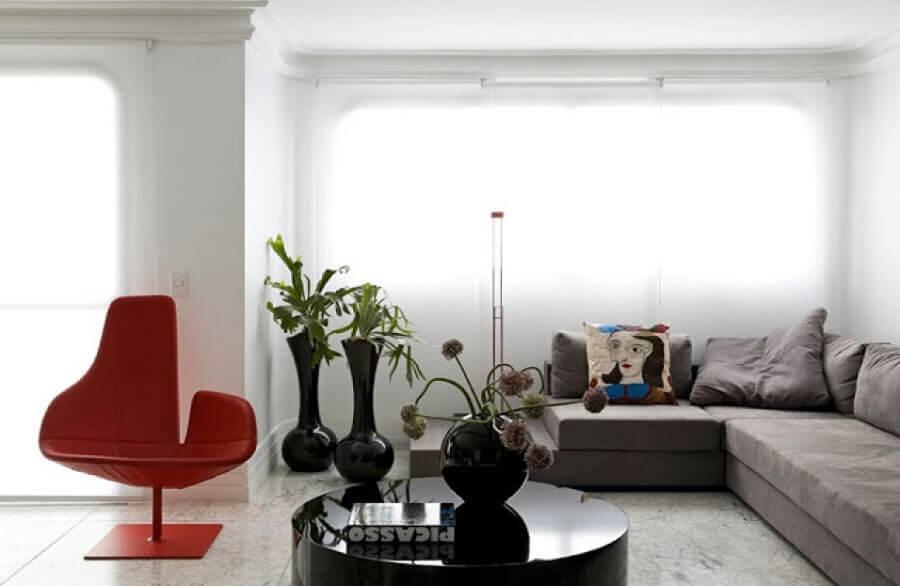 mesa de centro redonda preta para decoração de sala com poltrona vermelha moderna e vasos de chão  Foto eh!DÉCOR