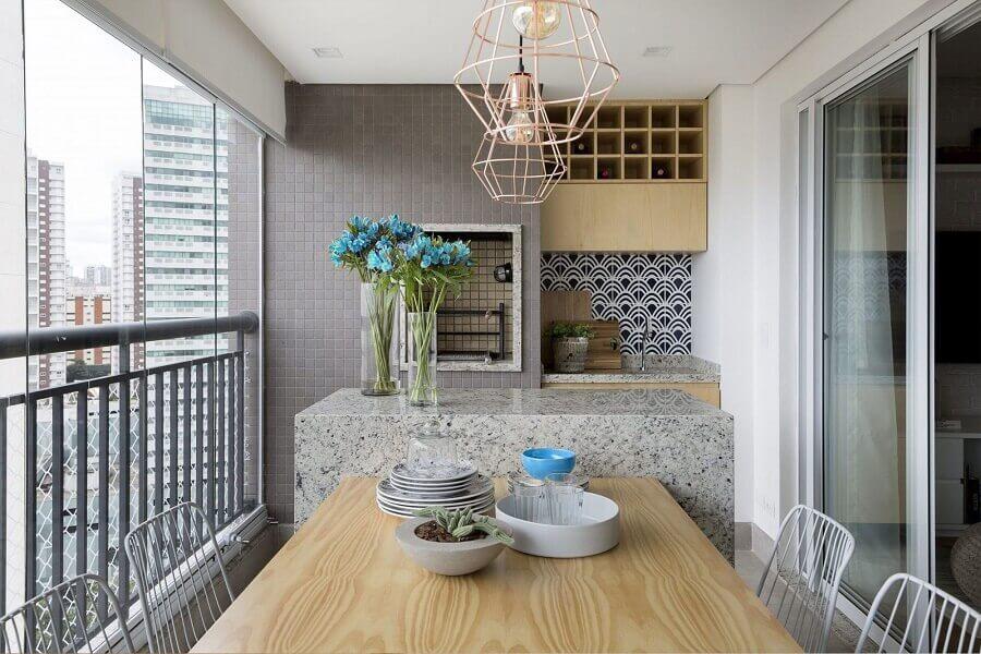 mesa de madeira com bancada de granito para varanda gourmet pequena com churrasqueira em apartamento  Foto DoobArquitetura