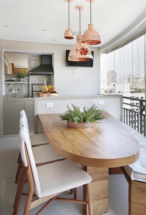 mesa de madeira planejada para decoração de varanda gourmet pequena com churrasqueira em apartamento  Foto Jeito de Casa