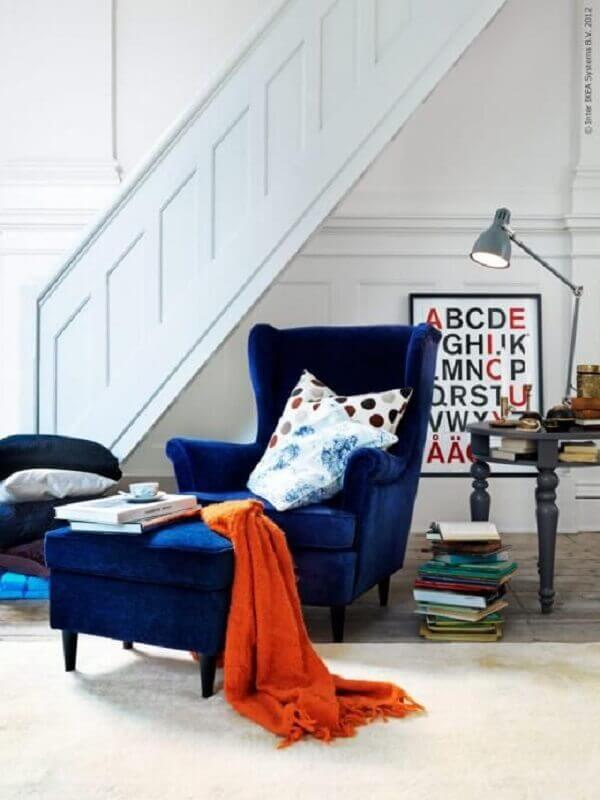 poltrona azul escuro decorada com manta laranja Foto Pinterest