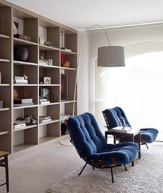 poltrona azul escuro para sala decorada com luminária de chão e estante de nichos  Foto Pinterest