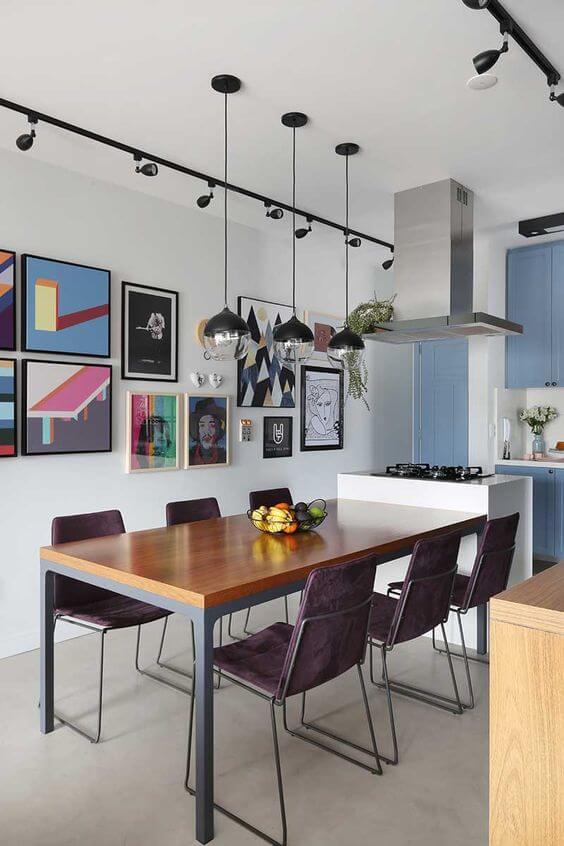 Mesa de jantar na varanda com quadros coloridos