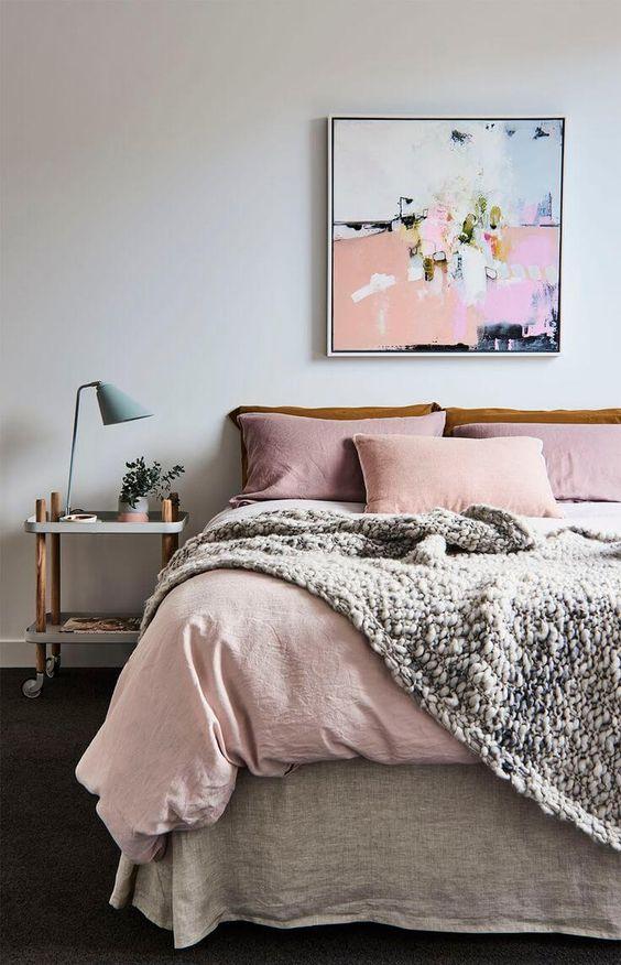 Quarto de casal com roupa de cama e almofada rosa