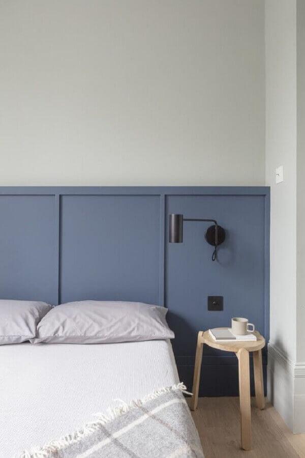 quarto minimalista decorado com luminária preta em cabeceira azul Foto ArchDaily