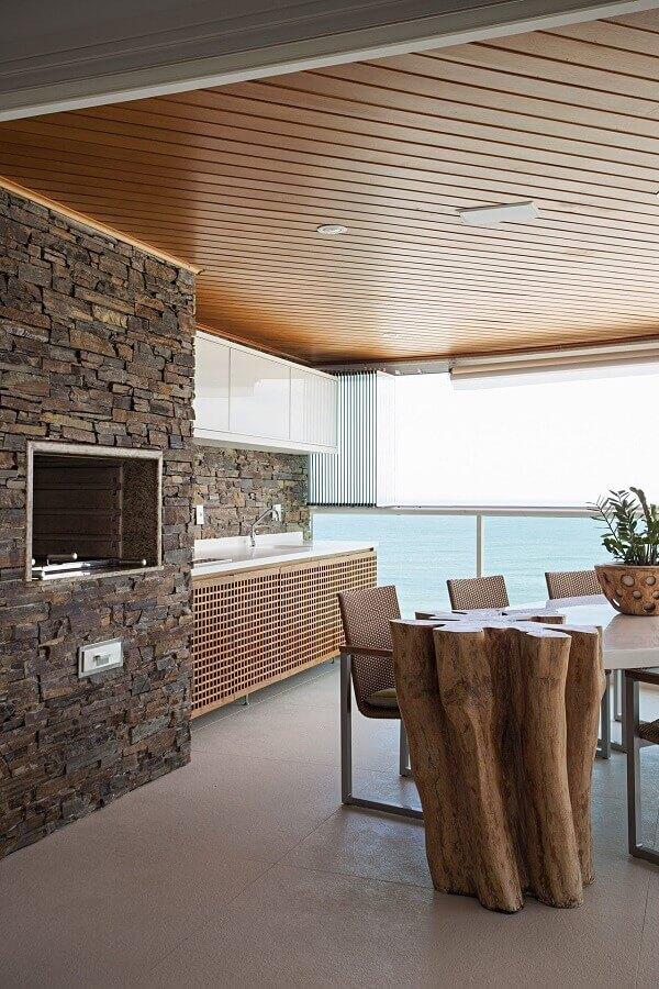 revestimento de pedra para de decoração de varanda gourmet rústica com churrasqueira em apartamento  Foto Korman Arquitetos