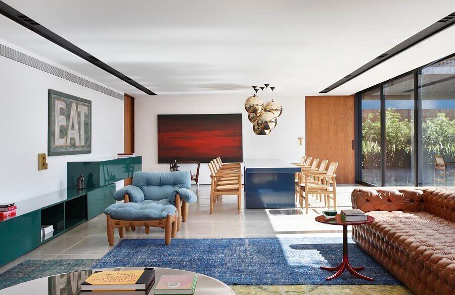 sala ampla decorada com sofá marrom capitonê e poltrona azul claro confortável Foto Guilherme Torres