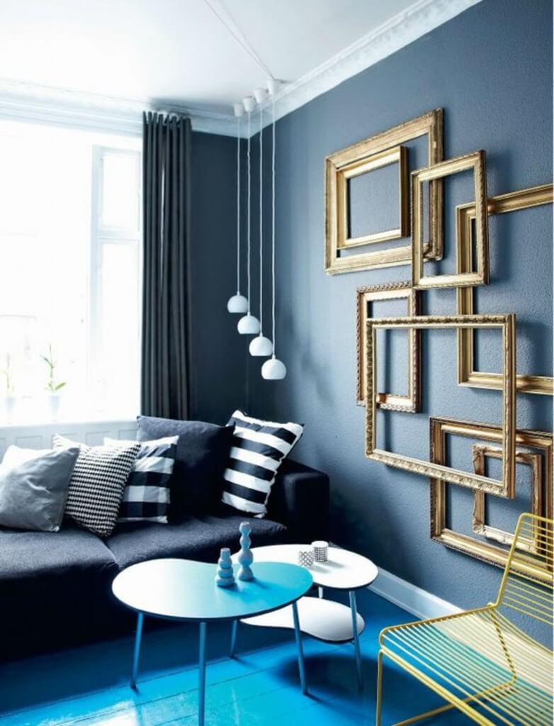 Sala azul monocromática com molduras de quadros na decoração