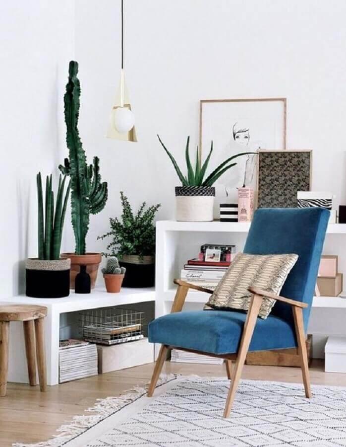 sala branca decorada com vasos de plantas e poltrona azul escuro de madeira  Foto Histórias de Casa