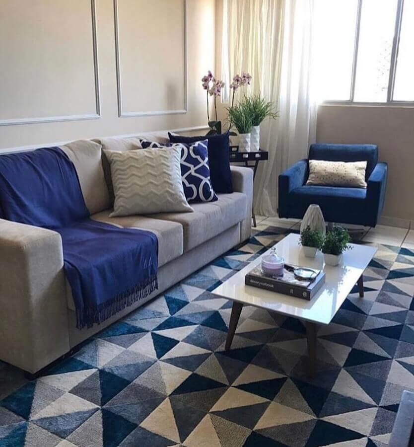 sala cinza decorada com manta e poltrona azul e tapete geométrico  Foto Pinterest