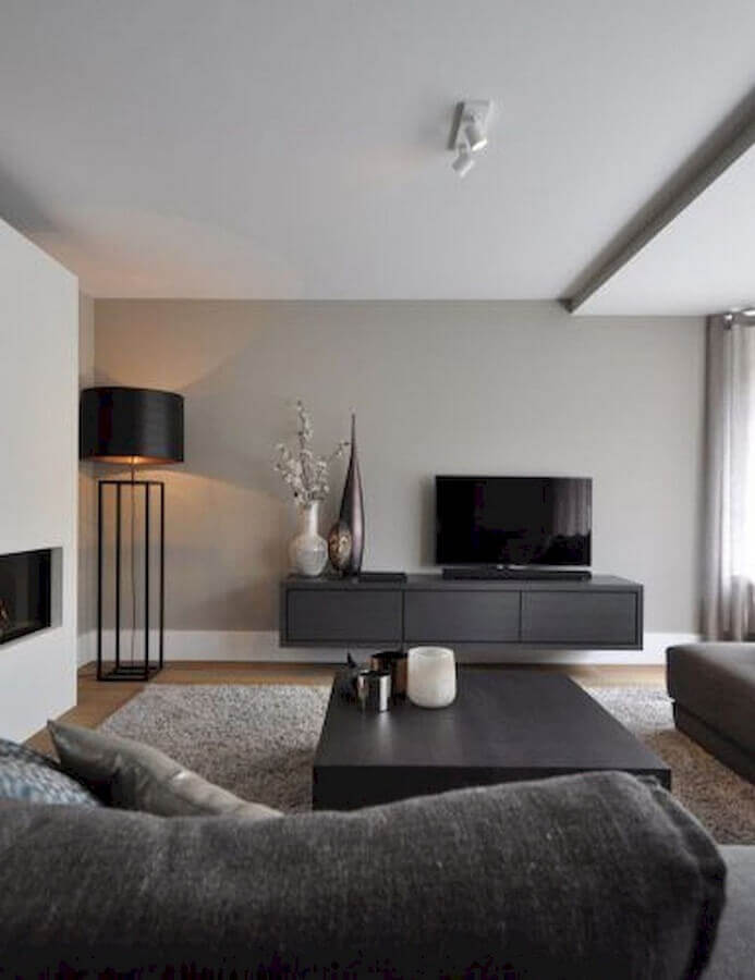 sala cinza moderna decorada com rack suspenso e mesa de centro preta  Foto Futurist Architecture