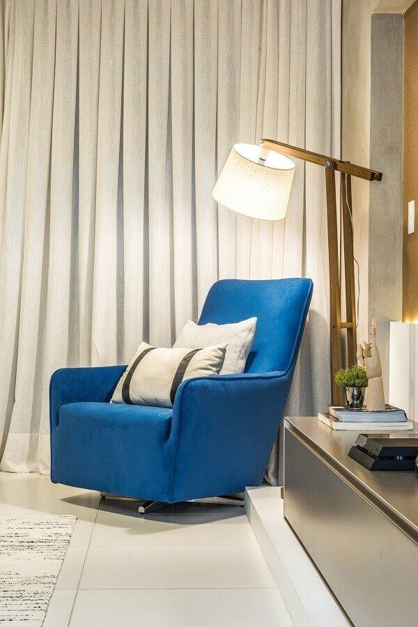 sala com poltrona azul confortável e abajur de chão  Foto Daniel Dantas