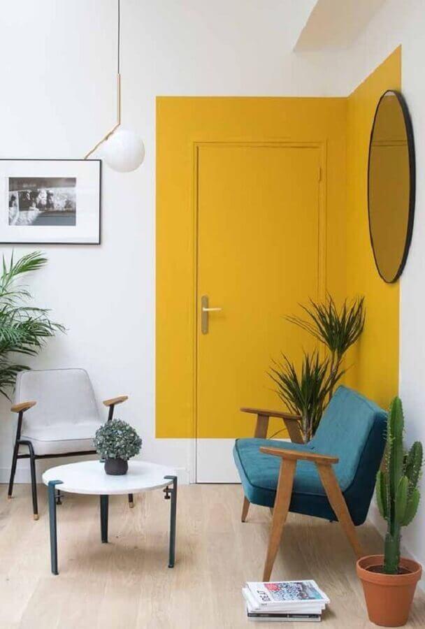 sala com poltrona azul simples e porta pintada de amarelo  Foto Manual da Obra