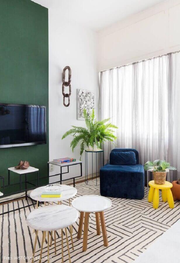 sala de TV decorada com poltrona azul escuro sem braço  Foto Histórias de Casa