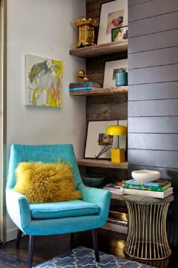 sala decorada com prateleira de madeira rústica e poltrona azul turquesa Foto Arquitrecos