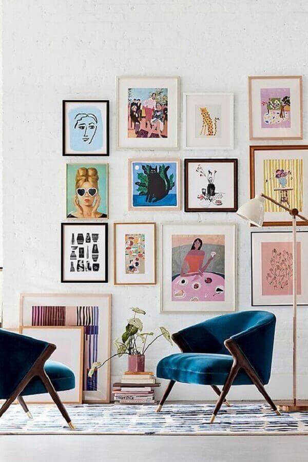 sala decorada com vários quadros e poltrona decorativa azul Foto Pump Up Decor