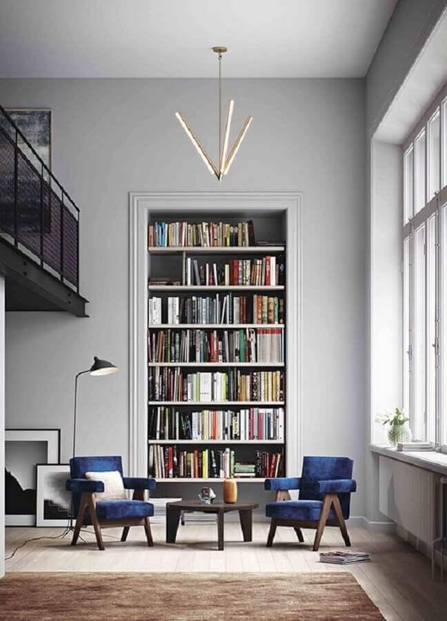 sala grande decorada com estante para livros planejada e poltrona decorativa azul Foto We Heart It