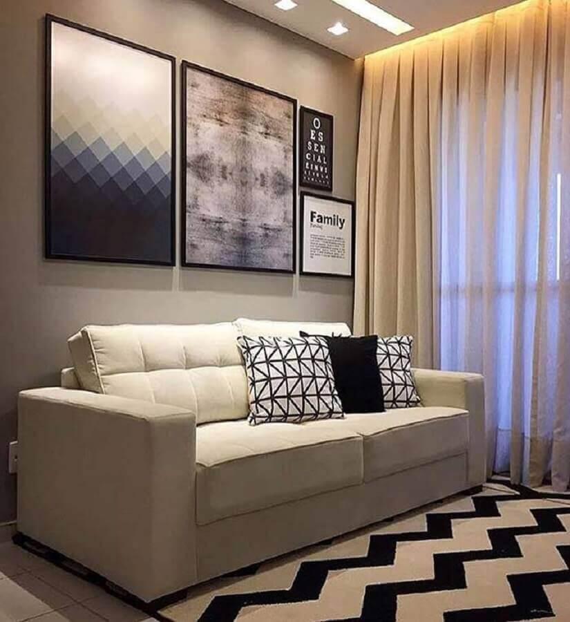 sofá pequeno para decoração de sala com quadros grandes e tapete preto e branco Foto Jeito de Casa
