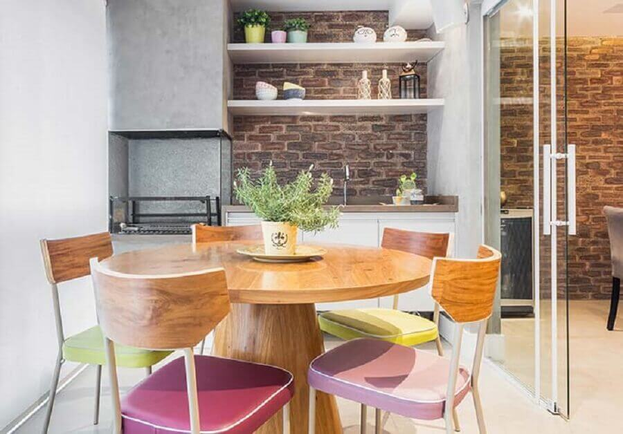 varanda gourmet pequena com churrasqueira em apartamento decorado com mesa redonda e cadeiras coloridas Foto Casa de Valentina