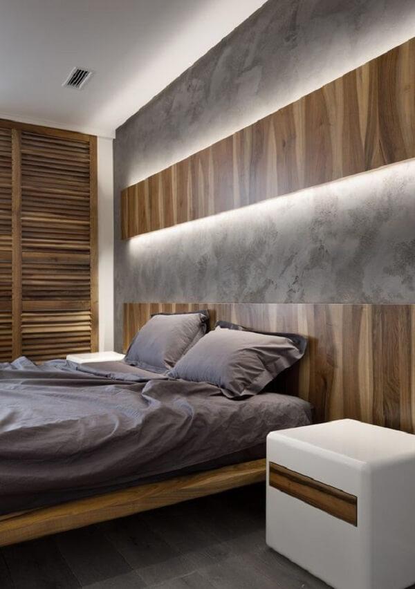 A arandela de madeira ocupa todo o espaço acima da cabeceira da cama