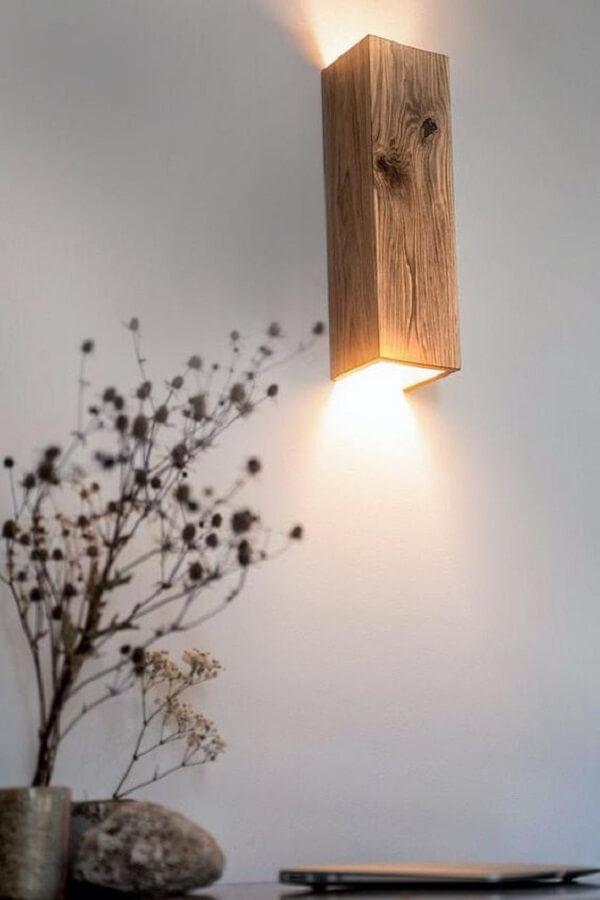 A arandela rústica de madeira se conecta com o restante da decoração