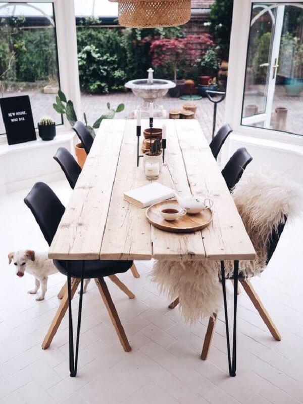 A cadeira preta se harmoniza facilmente com a mesa de madeira