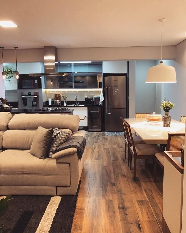 A cerâmica cor de madeira foi usada em todo o piso desse apartamento integrado
