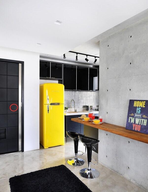 A placa de decoração colorida sobre a bancada de madeira traz alegria para a cozinha