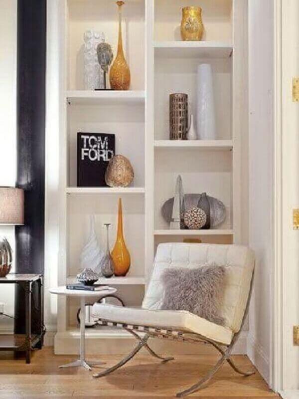 A poltrona barcelona branca se conecta com a estante repleto de artigos decorativos