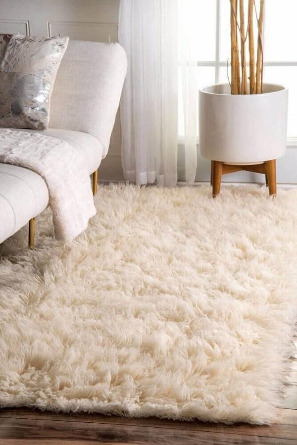 Ambiente com tapete shaggy branco e divã bege