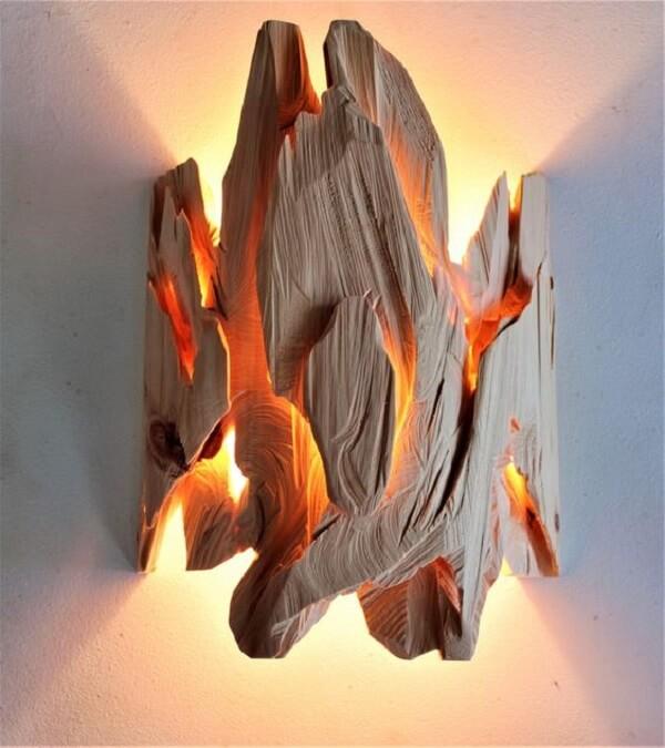 Arandela de madeira em formato assimétrico se destaca na parede