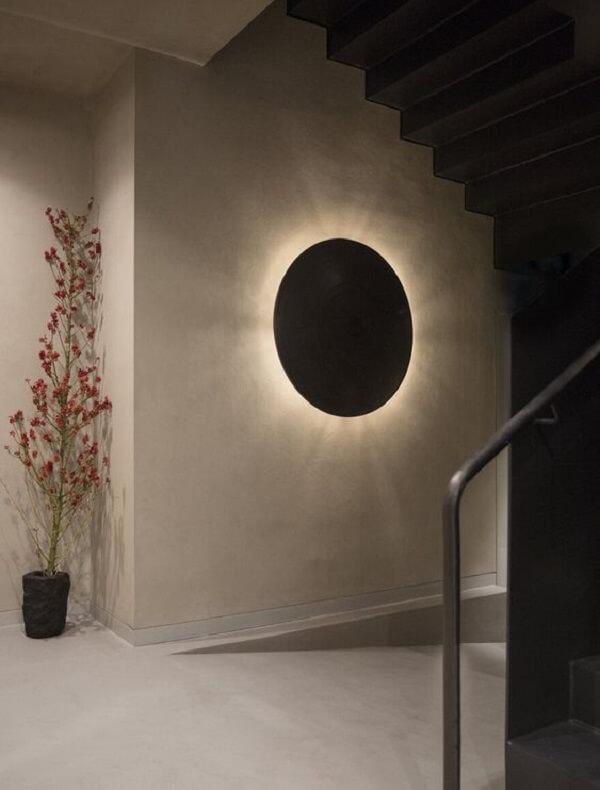 Arandela de madeira em formato redondo decora o hall de entrada