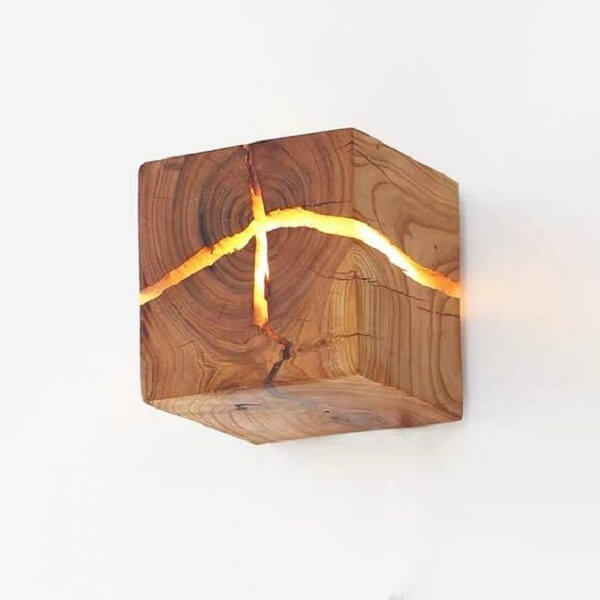 Arandela de madeira rústica com ranhuras que permitem a passagem da luz