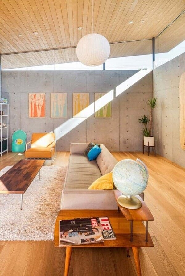 As cores de madeira clara do teto e piso conversam com o revestimento cimentício da parede