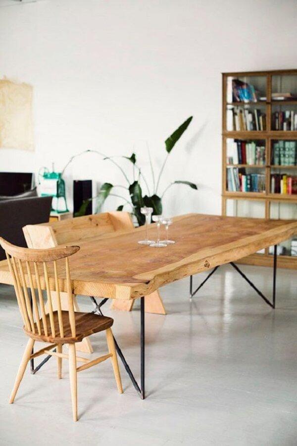 As cores de madeira com pés de ferro da mesa se destacam na sala de jantar