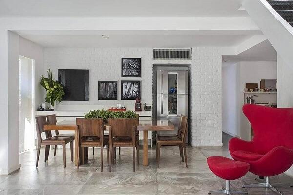 As cores de madeira para móveis escura como a mesa de jantar se contrastam com a parede branca