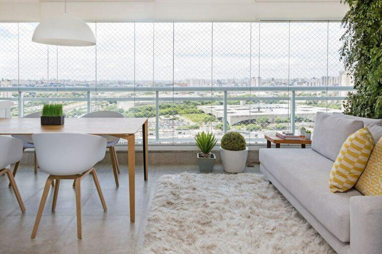 Cadeiras de couro branco e tapete shaggy bege complementa a decoração