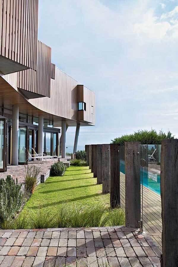 Casa moderna com muros decorados em madeira e vidr