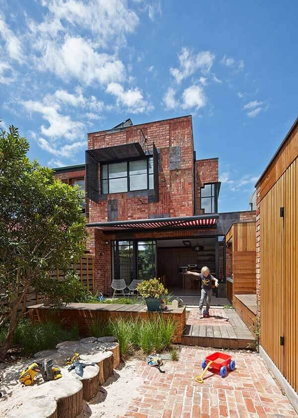 Casa sobrado com arquitetura rústica feita com tijolos