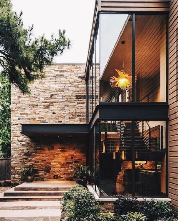 Casa sobrado com parede revestida de pedras e vasos decorativos