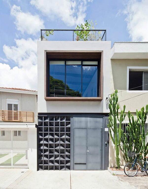 Casa sobrado com revestimento cinza e porta metálica