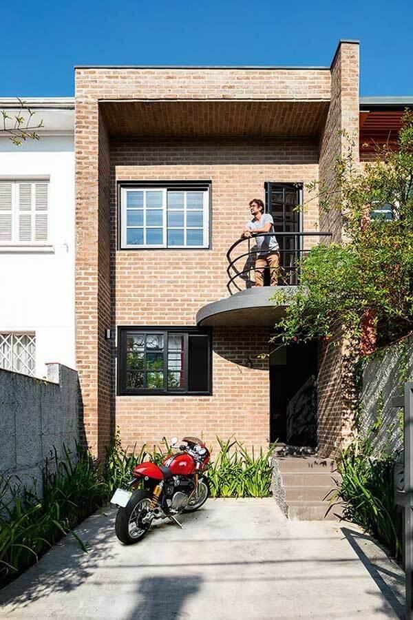 Casa sobrado pequeno com varanda oval e fachada em tijolinhos